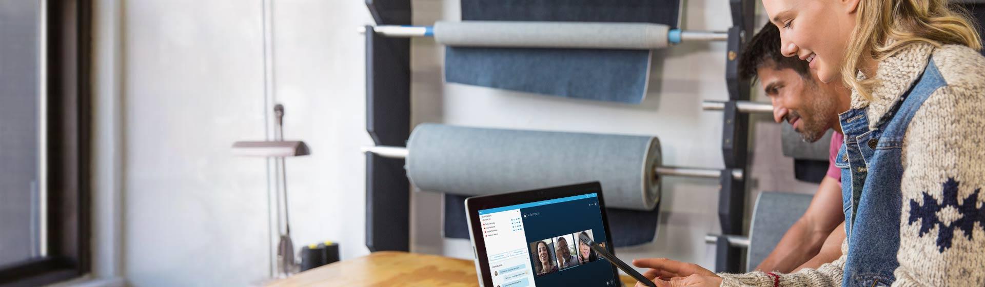 Mulher e homem usando as reuniões do Skype no tablet; a mulher está segurando a imagem de um telefone