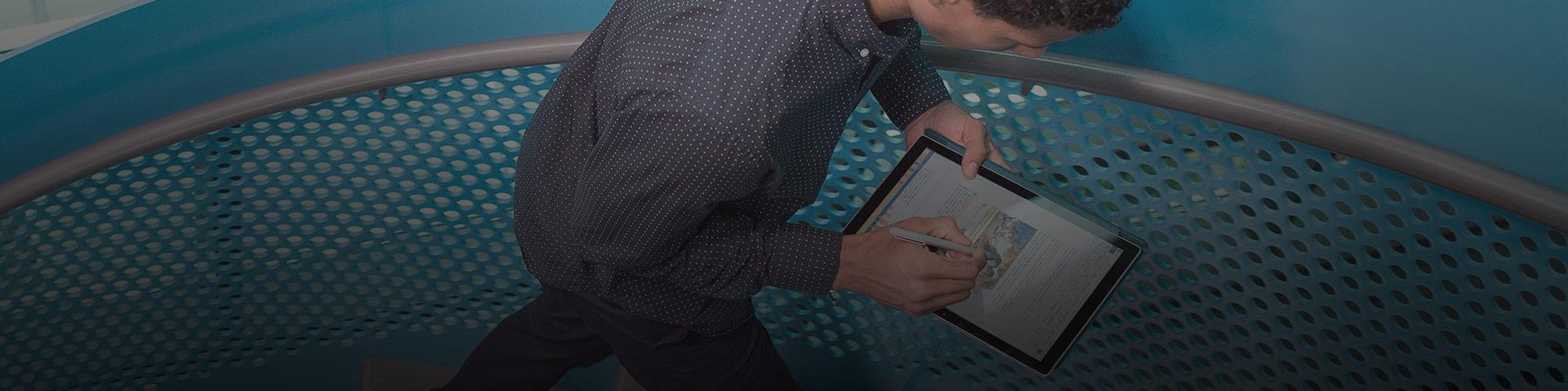 A imagem mostra um homem trabalhando em um tablet enquanto sobe uma escadaria