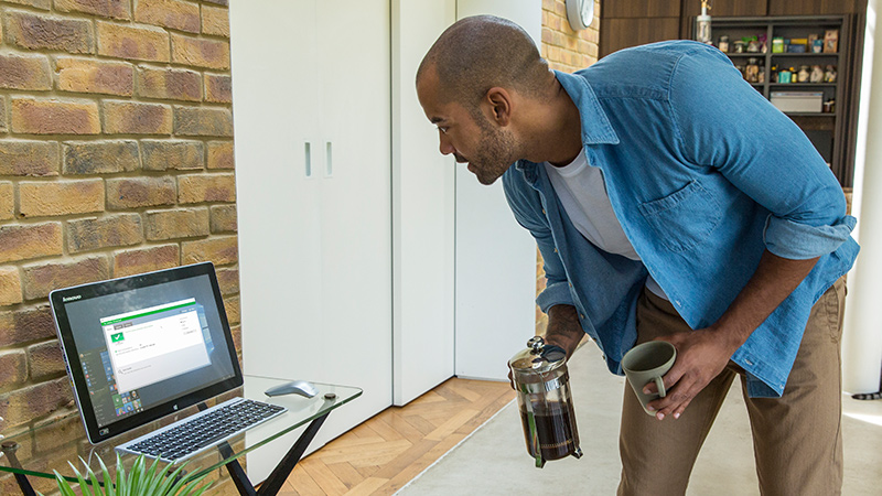 Homem olhando para a tela de um computador desktop em uma mesa de vidro e segurando uma cafeteira e uma caneca