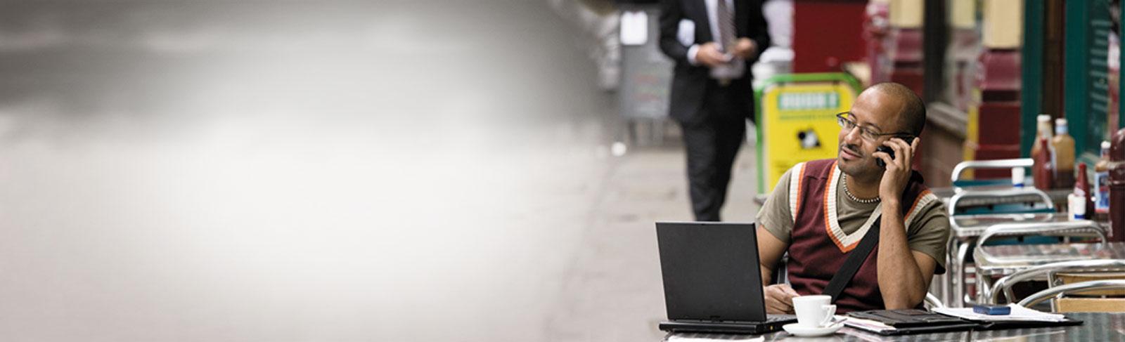 Um homem com um telefone e um laptop em um café, usando um email comercial via Exchange Server 2013.