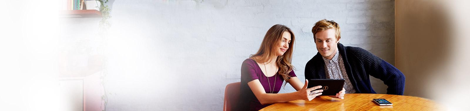 Uma mulher sentada em uma mesa, segurando um tablet e mostrando-o para um homem ao lado dela.