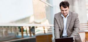 Um homem em pé, trabalhando em seu laptop e usando o Exchange Online.