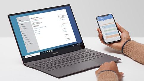 Uma pessoa a consultar o calendário no telemóvel enquanto um portátil Windows 10 implementa atualizações