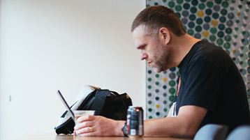 Um homem sentado à secretária a trabalhar no seu computador Windows10