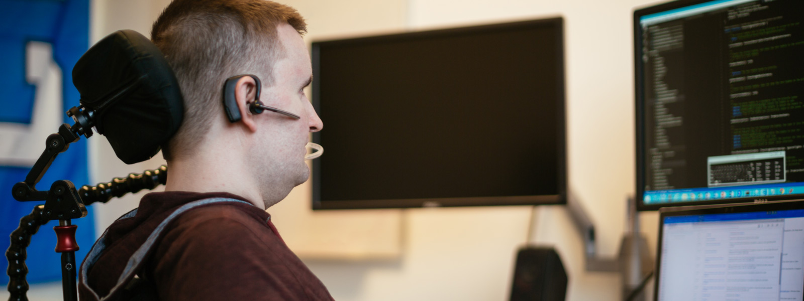 Um homem sentado à secretária a utilizar tecnologia de apoio de hardware para operar um computador Windows 10 através de controlo ocular