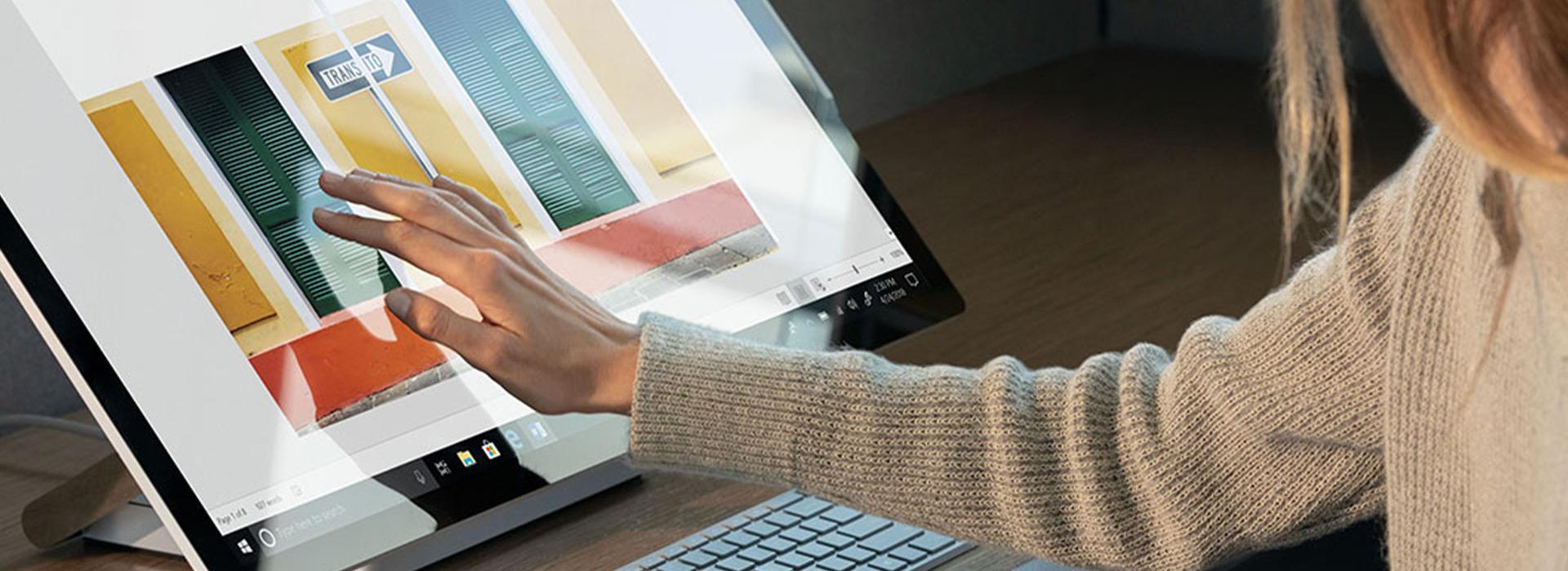 Uma mulher a utilizar o ecrã tátil do seu Surface Studio