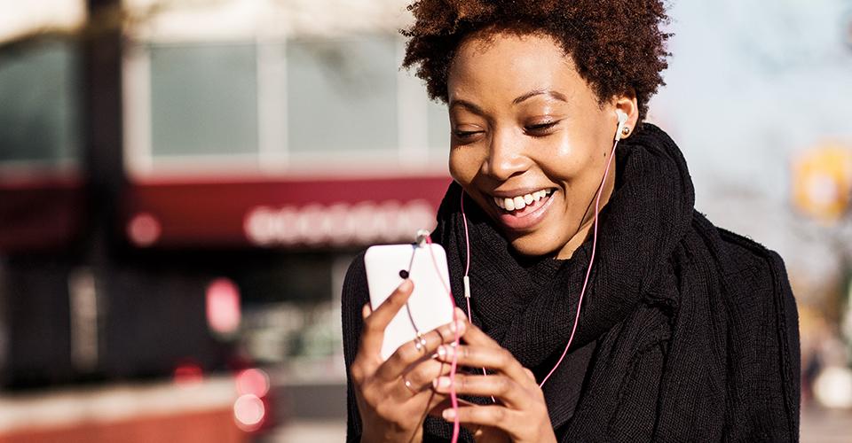 Uma mulher com roupa formal, com auriculares, a utilizar o seu dispositivo móvel num recinto exterior