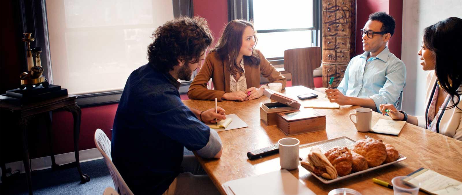 Quatro pessoas a trabalhar num escritório a utilizar o Office 365 Enterprise E3.