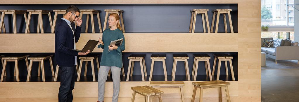 Um homem e uma mulher em pé a conversar com portáteis