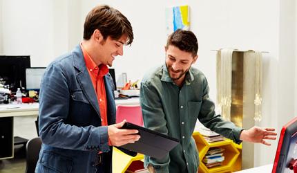 Dois homens em pé junto a um computador num escritório, a utilizar um tablet para colaborar.