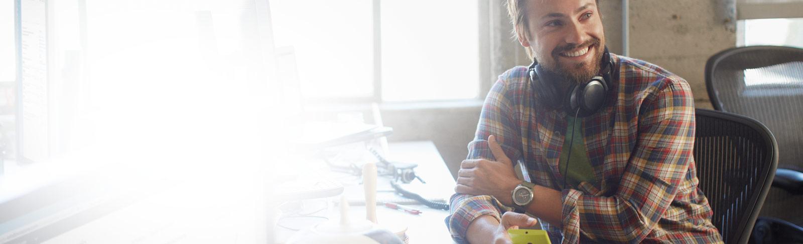 Um homem na sua secretária a segurar um telemóvel, a utilizar o Office 365 Enterprise E1.