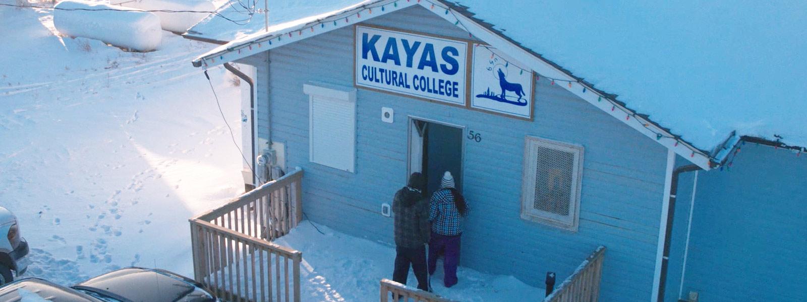 Vista exterior de um dos edifícios do Kayas Cultural College num dia de neve, com dois estudantes a entrarem.