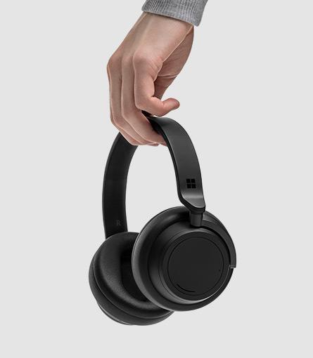 Um homem a segurar os Surface Headphones 2
