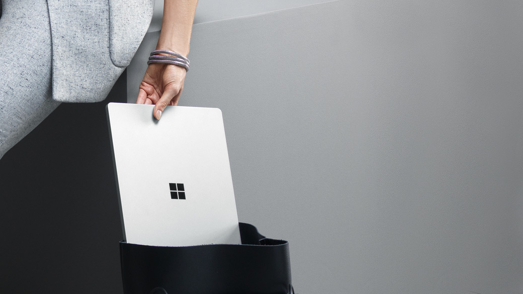 Mulher a tirar um Surface Laptop Platina de uma mala.