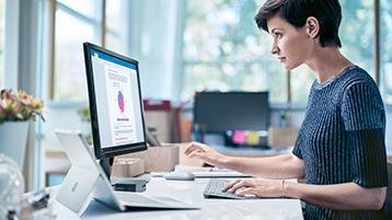 Mulher profissional bem vestida a utilizar um PC de secretária ligado a um dispositivo Surface.