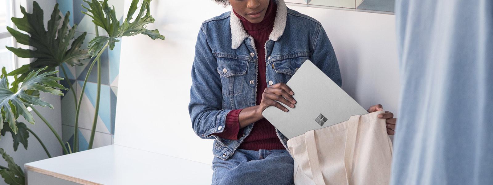 Imagem de uma estudante a guardar o Surface L na mala.