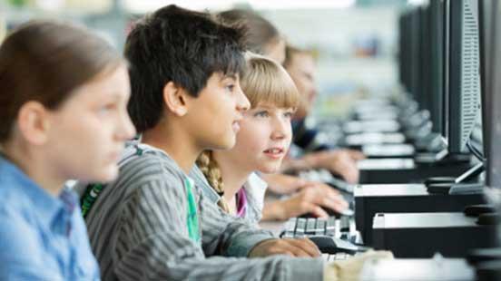 Crianças numa sala de aulas com computadores