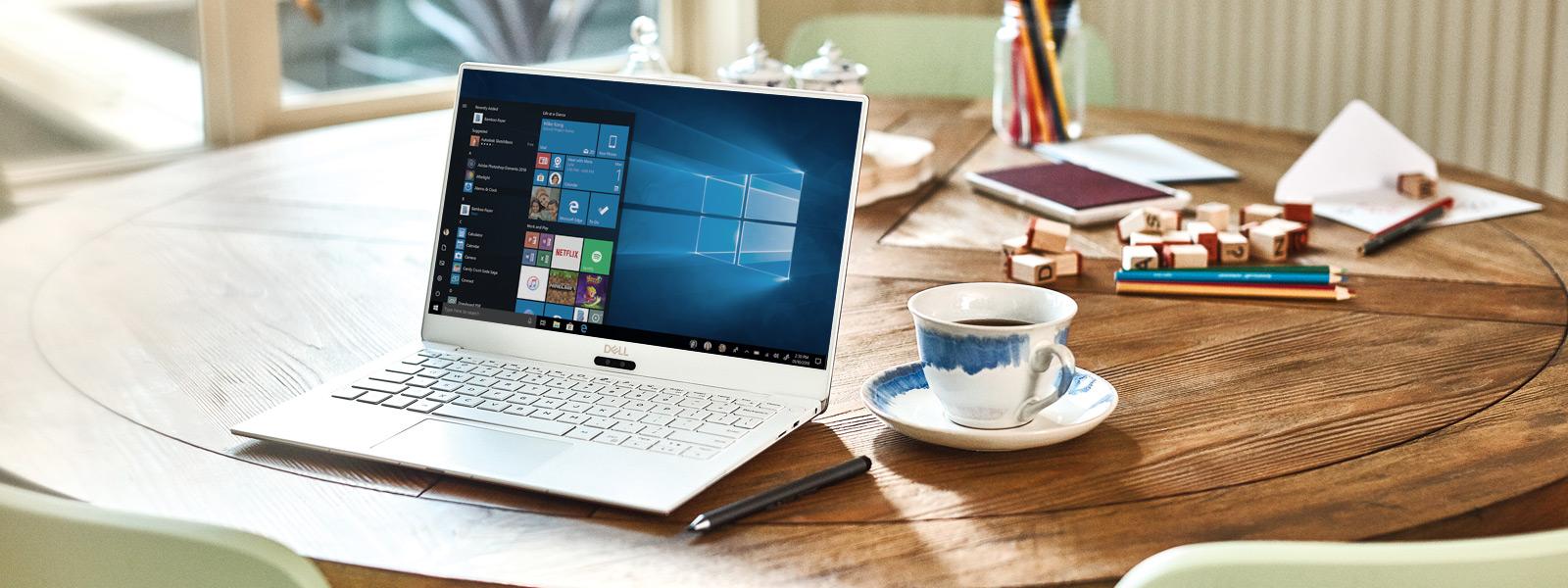 Un Dell XPS 13 9370 stă deschis pe o masă, afișând ecranul Start Windows 10.
