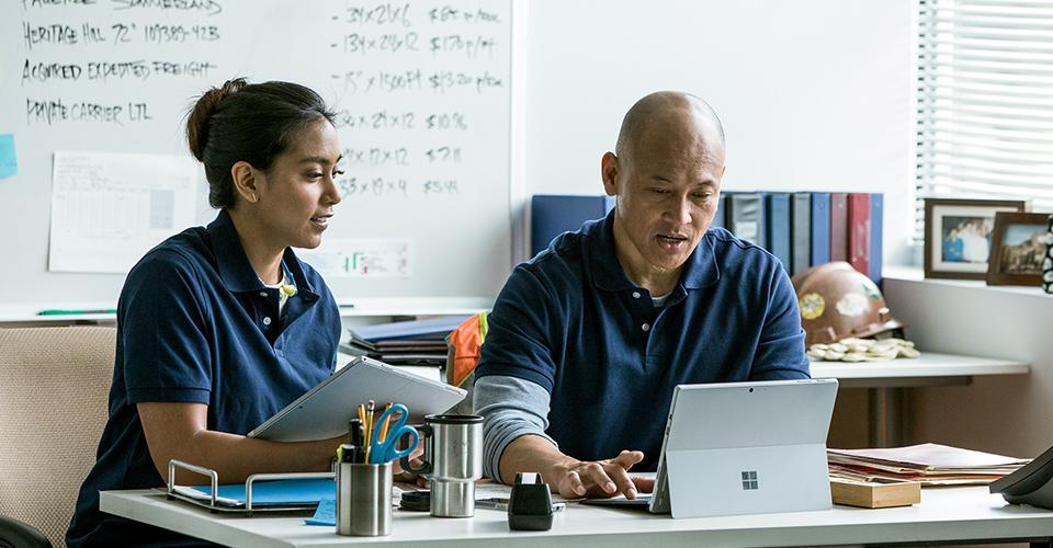 Un bărbat și o femeie lucrând împreună într-un birou