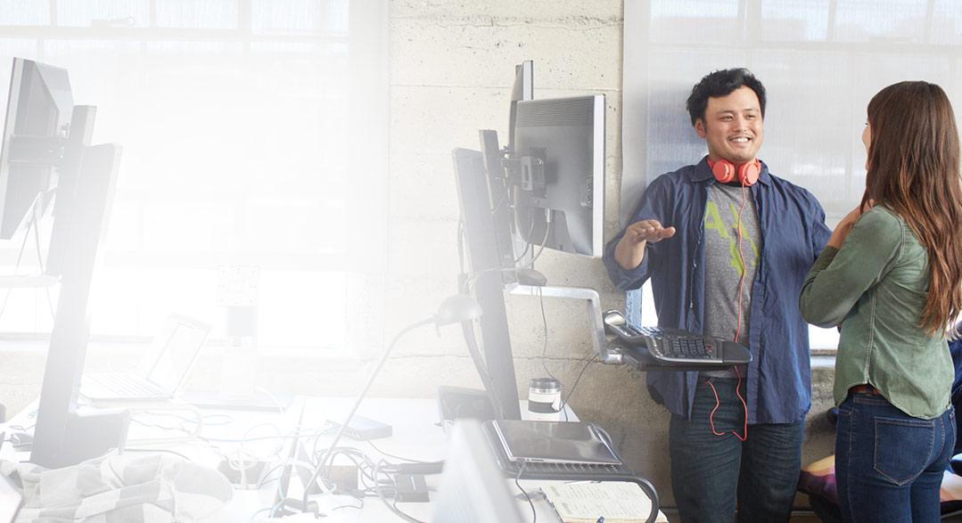 Un bărbat și o femeie în picioare, într-un birou, utilizând Office 365 Business Premium.