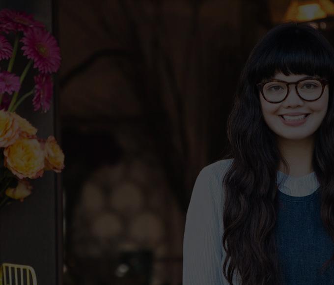 O femeie tânără cu ochelari, zâmbind, stând în aer liber lângă vaze cu flori.