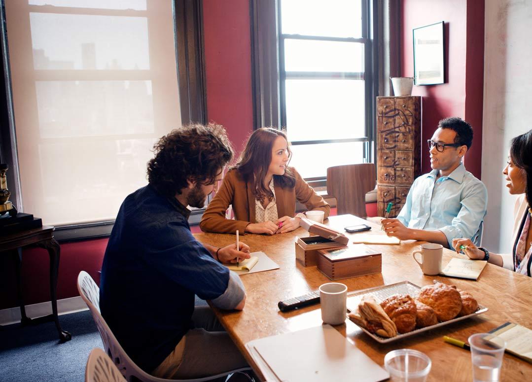 Patru  persoane care lucrează într-un birou, utilizând Office 365 Enterprise E3.