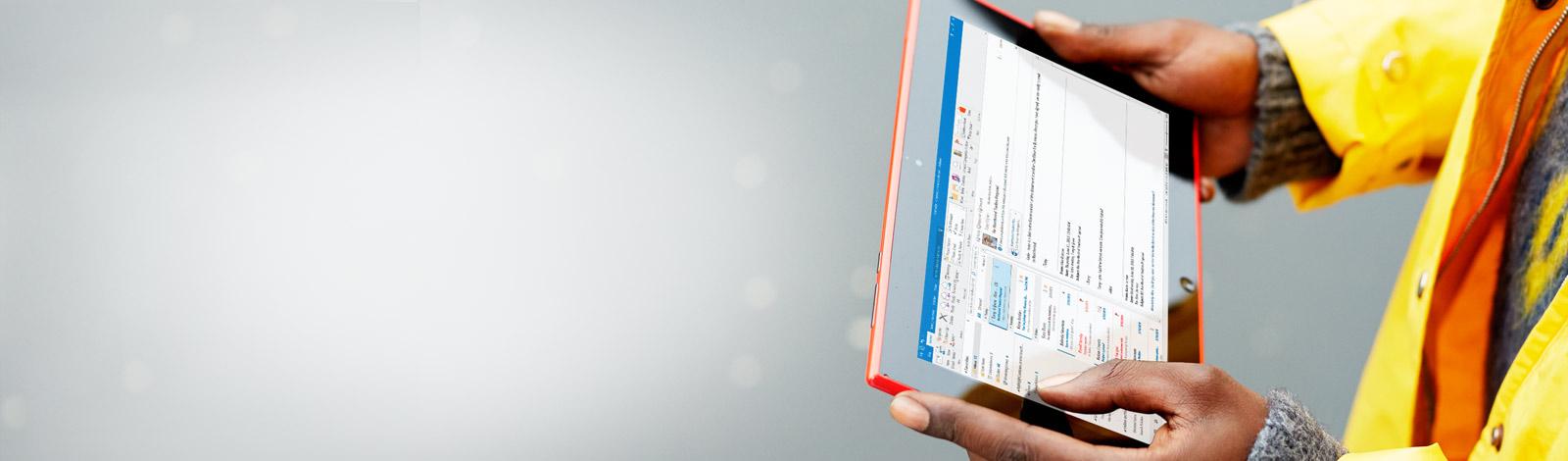 Un bărbat care ține o tabletă în mâini. Cu Office 365 puteți lucra de oriunde.