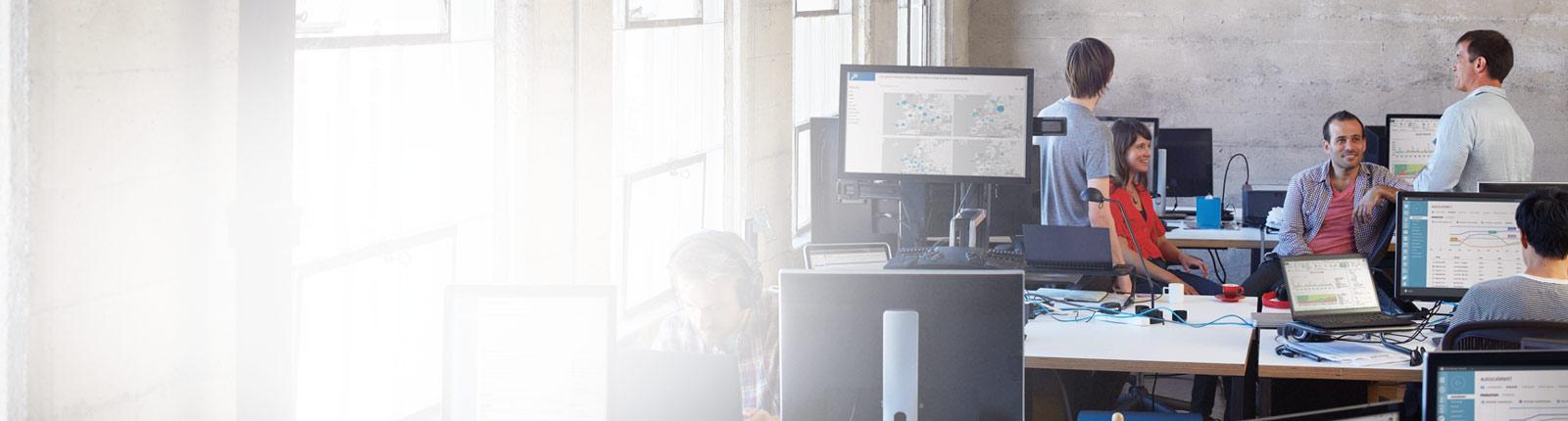 Cinci persoane care lucrează la desktopurile lor într-un birou, utilizând Office 365.