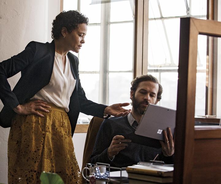 Două persoane într-un birou, privind spre un laptop Windows