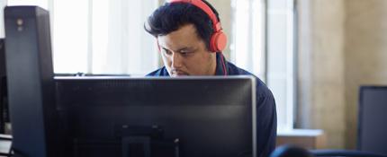 Un bărbat purtând căști, lucrând la un PC desktop. Office 365 simplifică mediul IT.