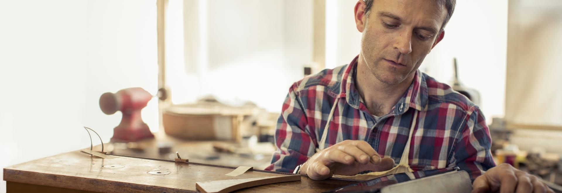 Un bărbat într-un atelier, utilizând Office 365 Business pe o tabletă