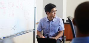 Un bărbat stând în fața unei table albe și lucrând la un laptop; aflați despre Protecția avansată împotriva amenințărilor Office 365