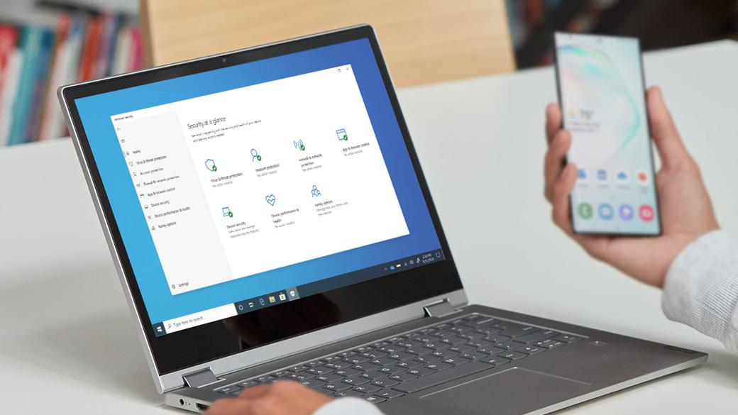 Человек просматривает сотовый телефон, в то время как на ноутбуке с Windows 10 отображаются функции безопасности