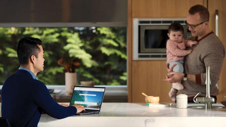 Мужчина на кухне держит и кормит ребенка напротив другого мужчины, который использует браузер Microsoft Edge на ноутбуке с Windows 10