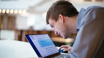 Человек смотрит в свой компьютер с Windows10, на экране которого отображается крупный удобочитаемый текст