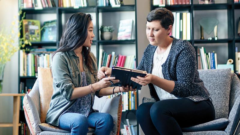две женщины пользующиеся одним планшетом