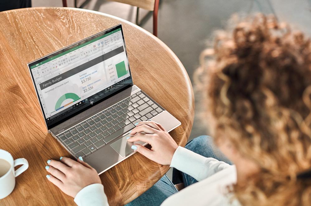 Сидящая за столом женщина с таблицей Excel на экране своего ноутбука