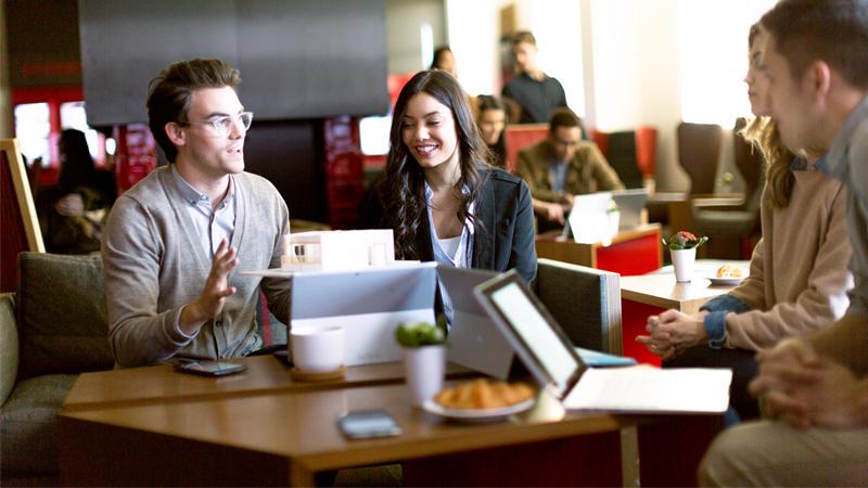 Люди, сидящие вокруг стола и работающие с ноутбуками