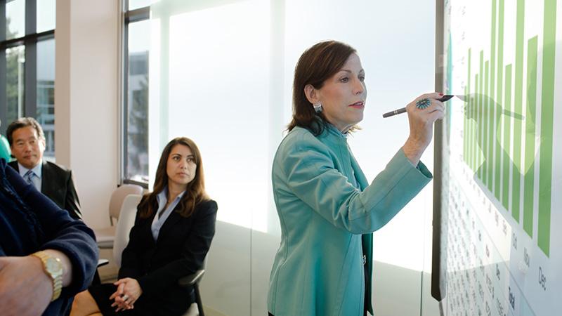 Женщина рисует диаграммы на большом экране