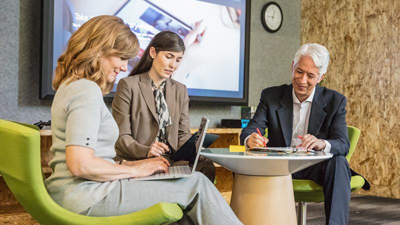 Деловые люди, сидящие вокруг стола и работающие с ноутбуками