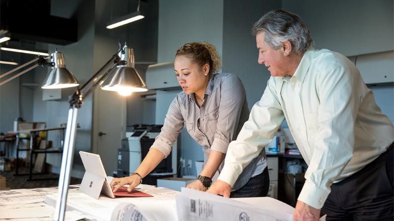 Мужчина и женщина работают с планшетом в офисе промышленного предприятия
