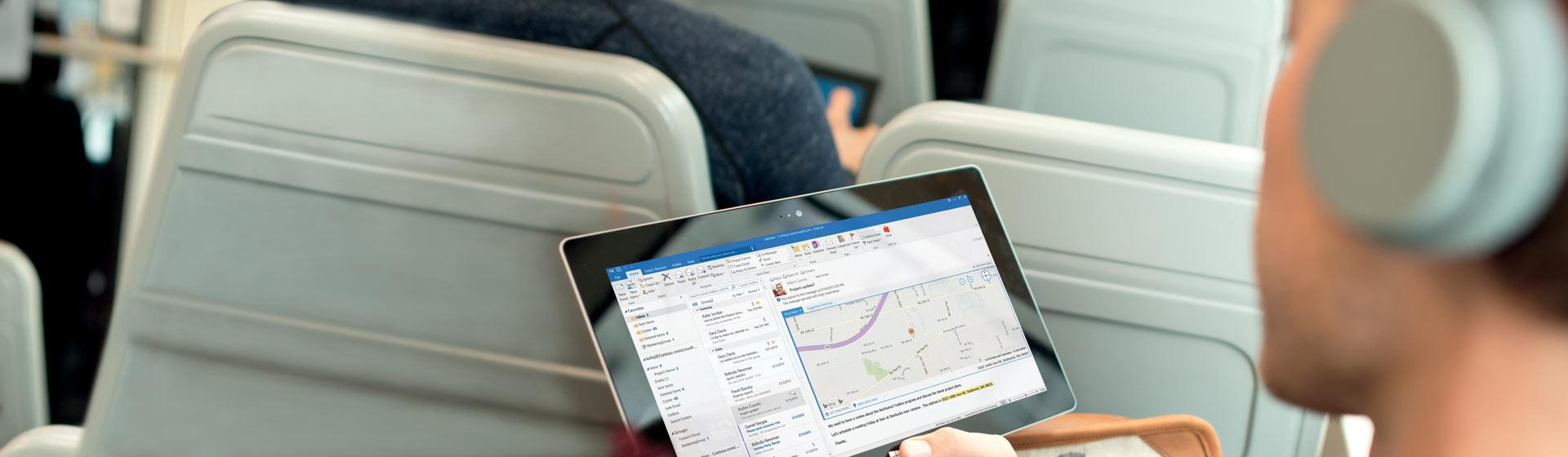 Мужчина с планшетом, на экране которого— папка входящих сообщений в Office365.