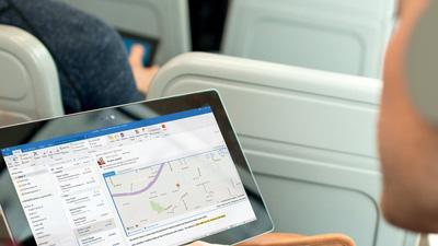 Мужчина смотрит на экран планшетного ПК с запущенным приложением Outlook