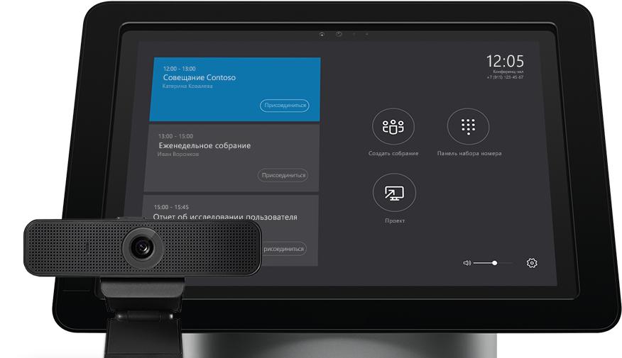 Устройство, на экране которого отображается расписание собраний, рядом с периферийным устройством для аудио- и видеосвязи