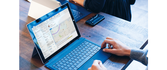 Мужчина работает с приложением Outlook на ноутбуке Microsoft Surface Book