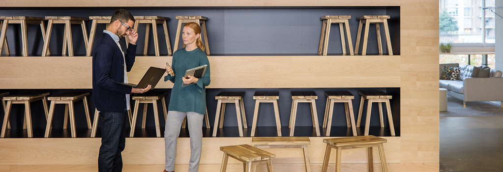 Мужчина и женщина с ноутбуками разговаривают стоя