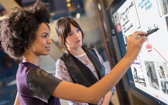 Две женщины работают с Delve на Surface Hub.