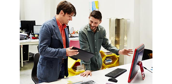 Два человека стоят у настольного компьютера в офисе и используют планшет для совместной работы.