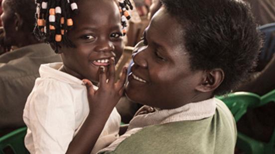 Маленькую девочку держат за руку, и она улыбается