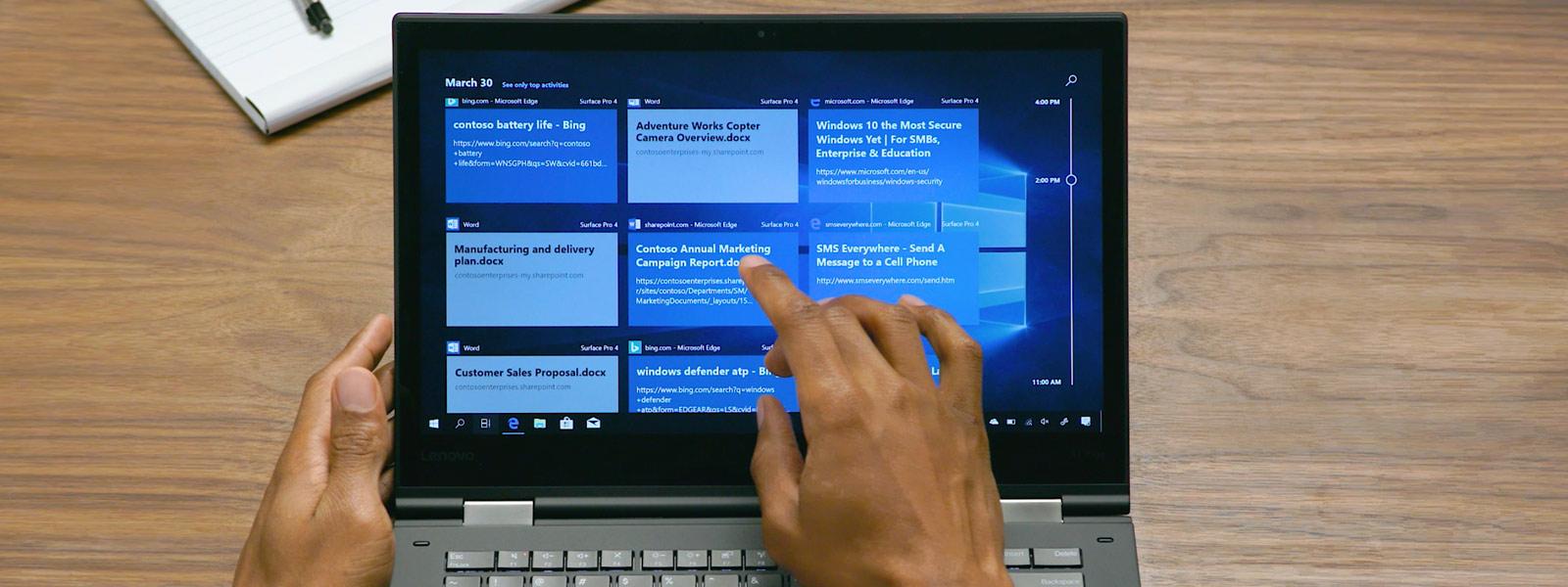 Мужчина пользуется сенсорным ноутбуком с функцией Windows Timeline на экране